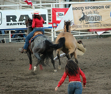 A night at the rodeo. Cody, Wyoming. Opening ceremony excitement results in a spooked horse and cowgirl on the ground.