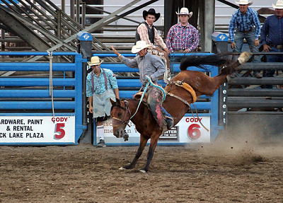 A night at the rodeo. Cody, Wyoming. Saddle bronc taking a cowboy for a ride.